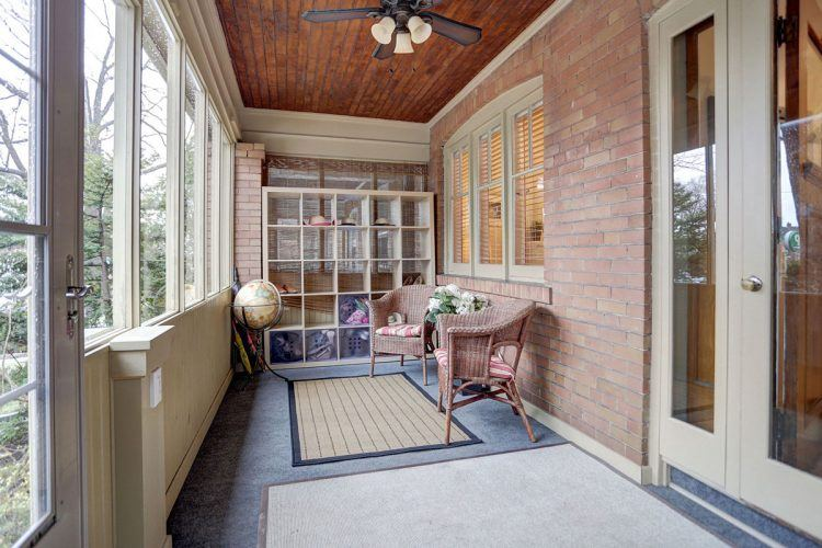 enclosed sitting area in front of house with wicker chairs