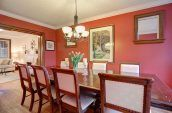 rectangular brown wooden dining table with chairs set beside wall