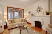 oval glass coffee table in living room with sofas and fireplace