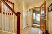 brown wooden door open in house foyer