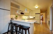 three brown stools in front of white kitchen counter