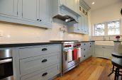 silver induction range oven between cupboards