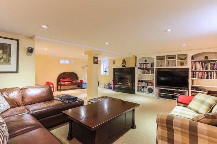 brown leather sofa in basedment with bookshelves tv and fireplace in the background