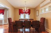 rectangular brown wooden dining table with chairs beside wall