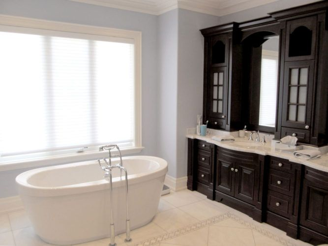 oval white bathtub beside wall inside room