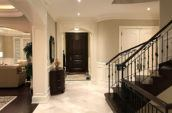 home foyer with black door staircase and tiled floors