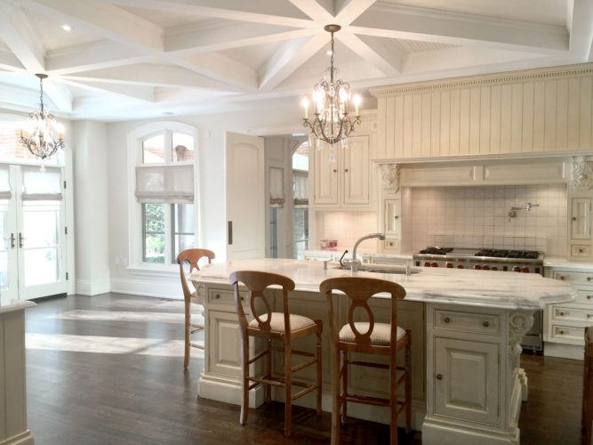 bright white kitchen with island and chandeliers