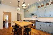 pendant lamps above dining set in kitchen with blue cabinetry