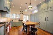 turned-on pendant lamps in kitchen with blue cabinetry