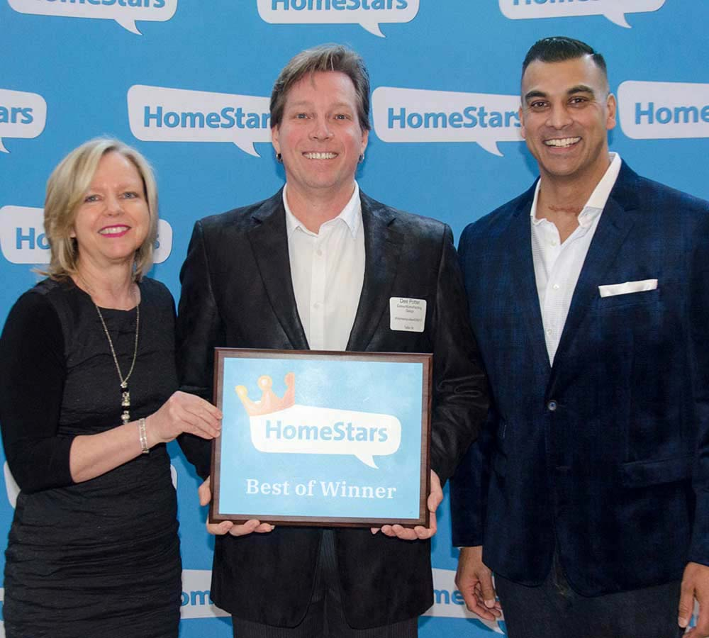 two smiling men standing beside woman holding framed homestars best of winner award
