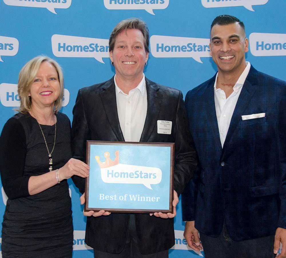two smiling men standing beside woman holding framed homestars best of winner award