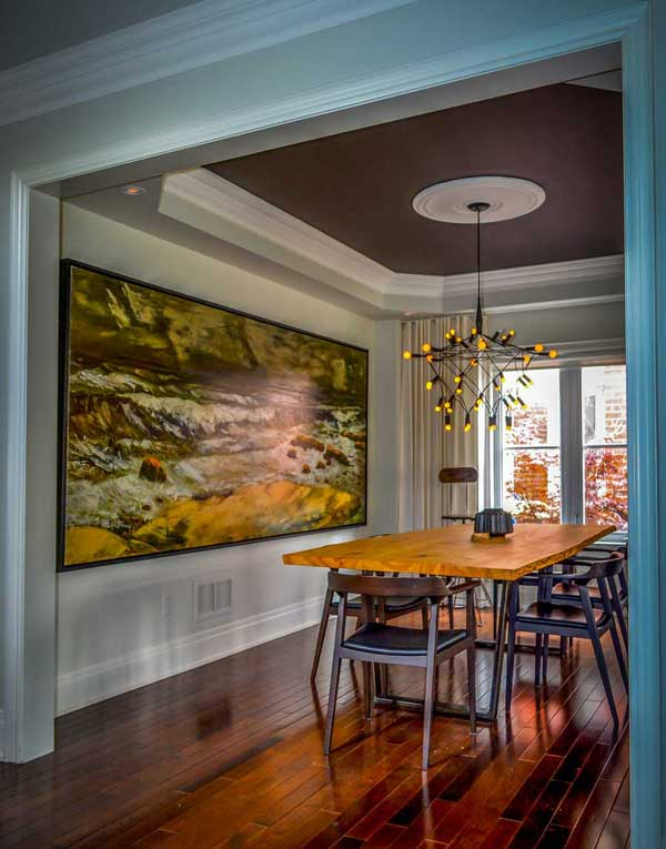 dining room with hardwood floors large painting on the wall wooden dining set and painted ceiling